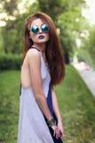 有蓝色嘴唇的可爱的深色的女孩在圆的太阳镜 免版税库存图片