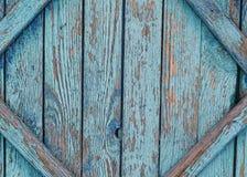 有蓝色破旧的油漆的老破裂的篱芭 免版税库存图片