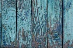 有蓝色破旧的油漆的老破裂的篱芭 库存照片