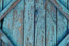 有蓝色破旧的油漆的老破裂的篱芭 免版税库存照片
