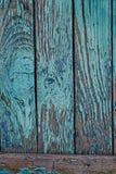 有蓝色破旧的油漆的老破裂的篱芭 图库摄影