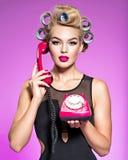 有蓝色culers的年轻可爱的妇女使用一个老电话 免版税库存图片