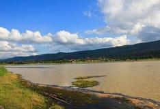 有蓬松云彩和山的湖 免版税图库摄影
