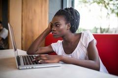 有蓬松卷发发型的美国黑人的妇女,穿戴在偶然白色上面,坐沙发在咖啡馆和等待她的朋友 破擦声 库存图片