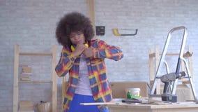 有蓬松卷发发型的非裔美国人的妇女得到伤害,当工作在车间时 股票录像