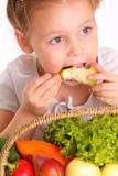 有蔬菜和水果的可爱的小女孩 图库摄影