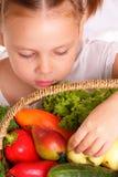 有蔬菜和水果的可爱的小女孩 免版税库存照片