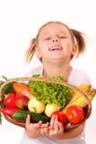 有蔬菜和水果的微笑的小女孩 免版税库存照片