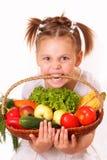 有蔬菜和水果的滑稽的小女孩 免版税库存照片