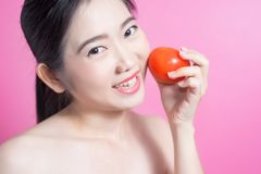 有蕃茄概念的亚裔妇女 微笑和拿着蕃茄的她 秀丽面孔和自然构成 隔绝在桃红色背景 库存照片