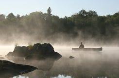 有薄雾乘独木舟的湖 免版税库存照片