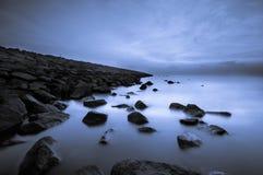 有薄雾的岩石跳船蓝色奥妙感受 库存图片