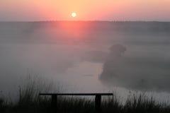 有薄雾的日出和空的长凳在一条小河 免版税图库摄影