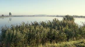 有薄雾的日出在一个湖夏天早晨 免版税库存照片
