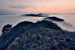 有薄雾的梦想的风景在秋天初期  在草甸、小山和镇的重的薄雾天际的 免版税库存图片
