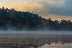 有薄雾的湖在与五颜六色的云彩的早晨在天空 免版税库存照片