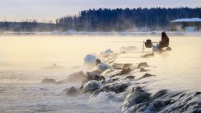 有薄雾的湖的一位孤立渔夫有一根钓鱼竿的,清早,冬天 免版税库存图片