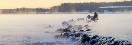 有薄雾的湖的一位孤立渔夫有一根钓鱼竿的,清早 免版税库存照片