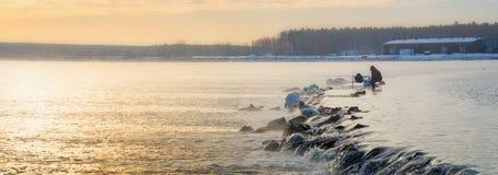有薄雾的湖的一位孤立渔夫有一根钓鱼竿的,清早 免版税图库摄影