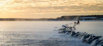 有薄雾的湖的一位孤立渔夫有一根钓鱼竿的,清早 库存照片