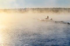 有薄雾的湖的一位孤立渔夫有一根钓鱼竿的,清早 库存图片