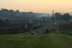 有薄雾的路在早上和黄色天空 免版税库存照片