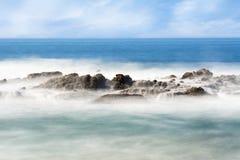 有薄雾的近海礁石 库存图片
