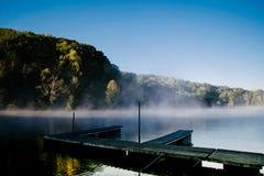 有薄雾的Morning湖的小船船坞 免版税库存图片