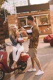 有薯条的男朋友哺养的女朋友在食物附近 免版税图库摄影