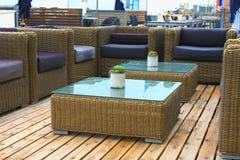 有藤条扶手椅子的大阳台休息室在海滩 图库摄影