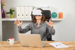 有虚拟现实耳机和膝上型计算机的女实业家在workpla 免版税图库摄影