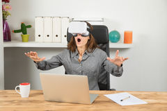 有虚拟现实耳机的惊奇女实业家在工作场所 免版税库存照片
