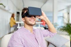 有虚拟现实耳机的愉快的人在办公室 免版税库存图片