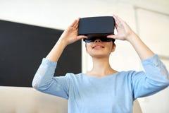 有虚拟现实耳机的愉快的妇女在办公室 免版税库存照片