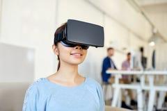 有虚拟现实耳机的愉快的妇女在办公室 库存图片
