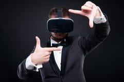 有虚拟现实glassess的英俊的富有的人 库存照片