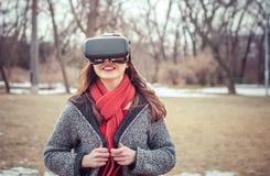 有虚拟现实VR耳机微笑的美丽的女孩 库存照片