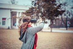 有虚拟现实VR耳机的女孩在街道上 免版税库存照片