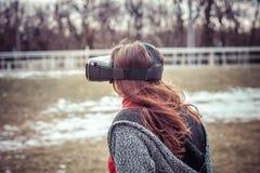 有虚拟现实VR耳机的女孩在街道上 免版税图库摄影