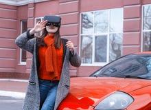 有虚拟现实VR耳机的美丽的女孩在红色spor 免版税库存照片