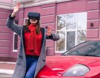 有虚拟现实VR耳机的美丽的女孩在红色spor 免版税库存图片