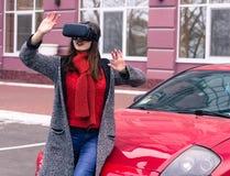 有虚拟现实VR耳机的美丽的女孩在红色spor 库存照片