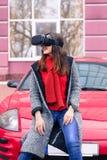 有虚拟现实VR耳机的美丽的女孩在红色spor 库存图片