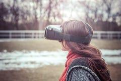 有虚拟现实VR耳机的美丽的女孩在stre 免版税库存图片