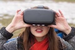 有虚拟现实VR耳机的美丽的女孩 免版税图库摄影