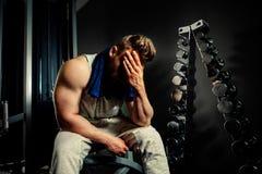 有蛋白质振动器和毛巾的疲乏的爱好健美者运动员在健身房 免版税库存照片