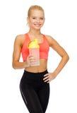 有蛋白质震动瓶的微笑的运动的妇女 免版税库存图片