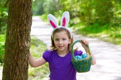 有蛋篮子和滑稽的兔宝宝耳朵的复活节女孩 免版税库存图片