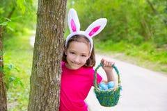 有蛋篮子和滑稽的兔宝宝面孔的复活节女孩 免版税库存照片