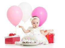 有蛋糕、气球和礼物的女婴 免版税图库摄影